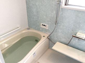 バスルームリフォーム 爽やかなグリーンのパネルが目を引く、温かく広々とした浴室