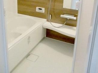 バスルームリフォーム 木目調の壁パネルと電球色のライトで落ち着いた雰囲気の浴室