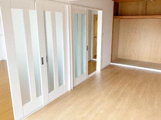 内装リフォーム 明かり取りのついた白い間仕切り戸が映える洋室